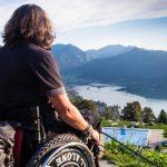 Ich, im Rollstuhl, von hinten, blicke von der Schliersbergalm über den Schliersee in Richtungalpen